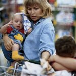 Mother and two children (1-6) shopping in supermarket