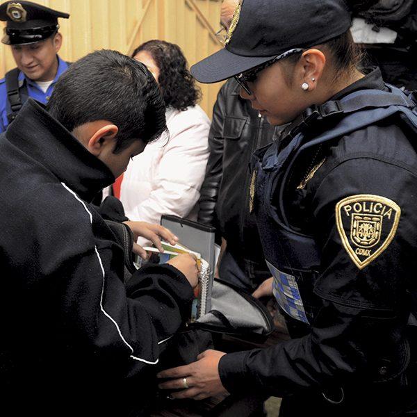 Policías revisan las mochilas de estudiantes de nivel básico durante el operativo Mochila Segura. Foto, Cuartoscuro.